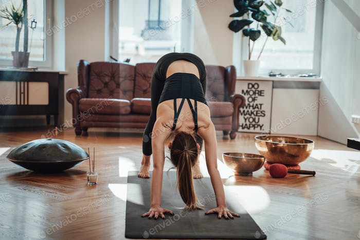 Slim caucasian woman working out in living room with sunbeams
