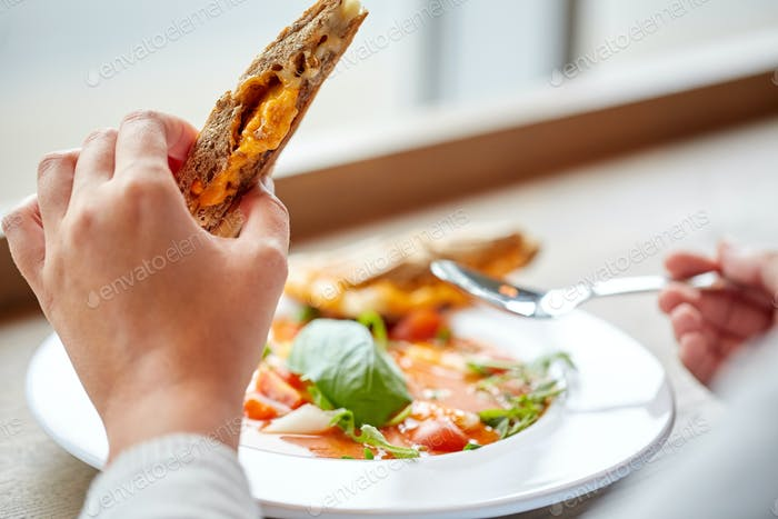close up of woman eating soup with sandwich