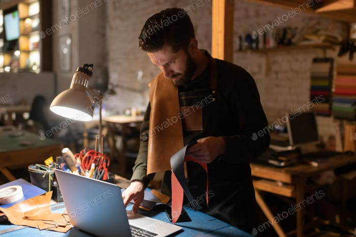 Serious man with leather browsing laptop