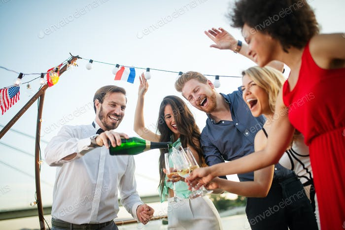 Group of happy friends drinking champagne and celebrating New Year