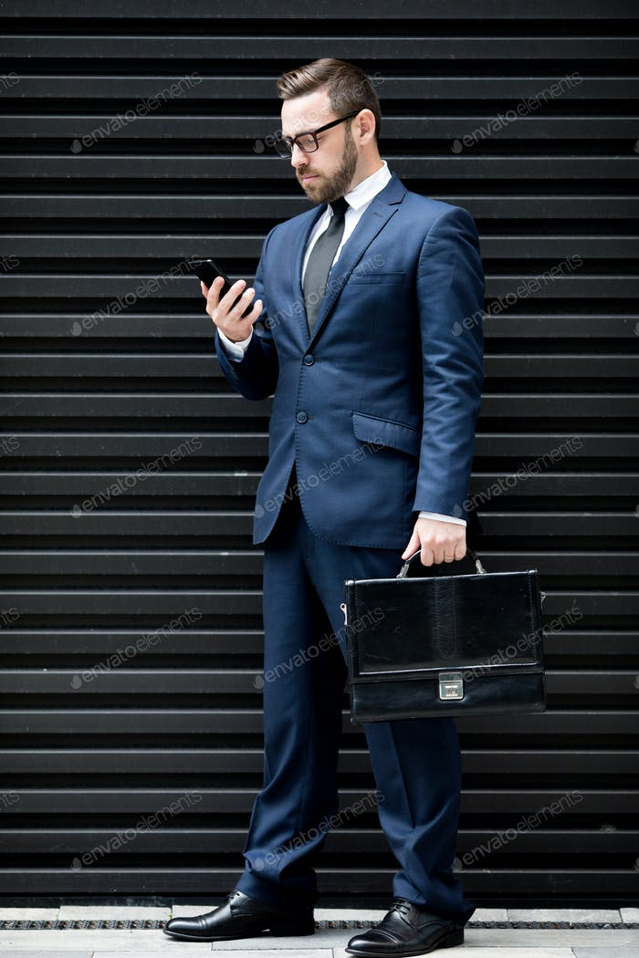 Concentrated business man with smartphone and briefcase