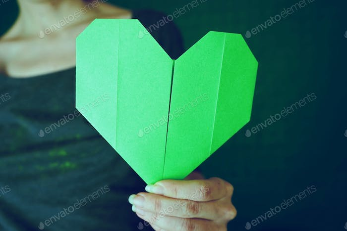 Woman holding a paper green heart