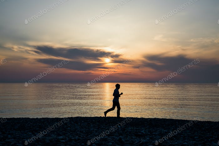 Silhouette of sport active man running and exercising on the beach at sunset