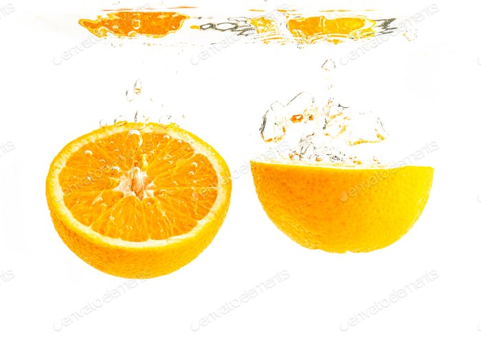 Organic orange sliced in half sinking into crystal clear water with air bubbles