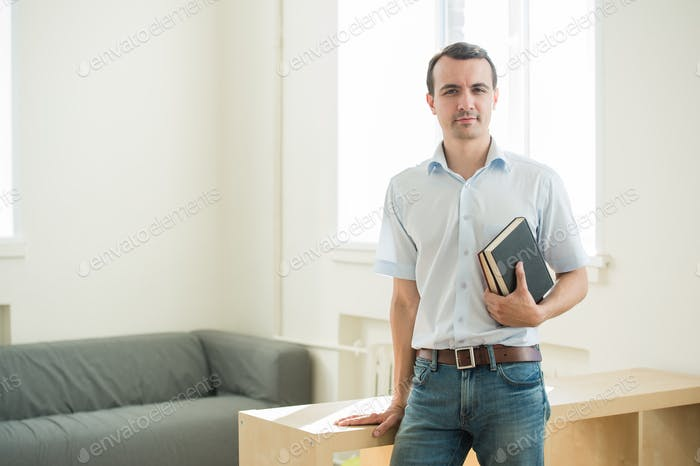 Closeup portrait, young business man or teacher in blue shirt reading, perusing books at school