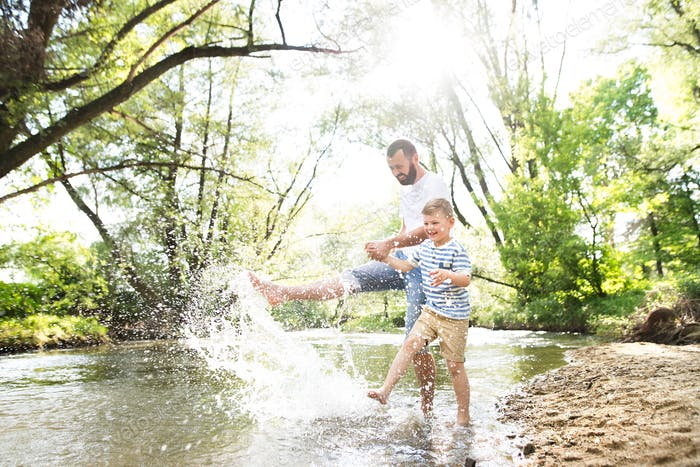 Young father with little boy in the river, sunny spring day.