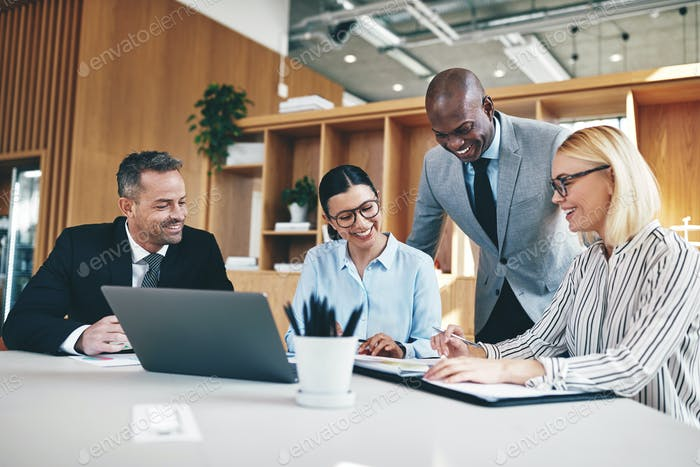 Diverse group of businesspeople laughing together during an office meeting