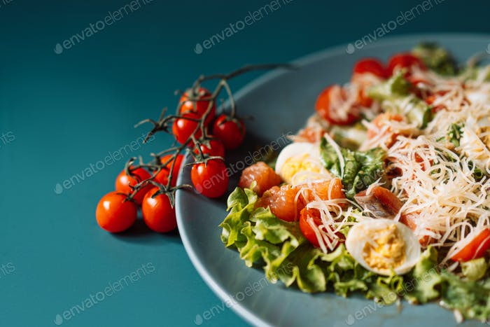 Plate with salad and cherry tomatoes on turquoise background
