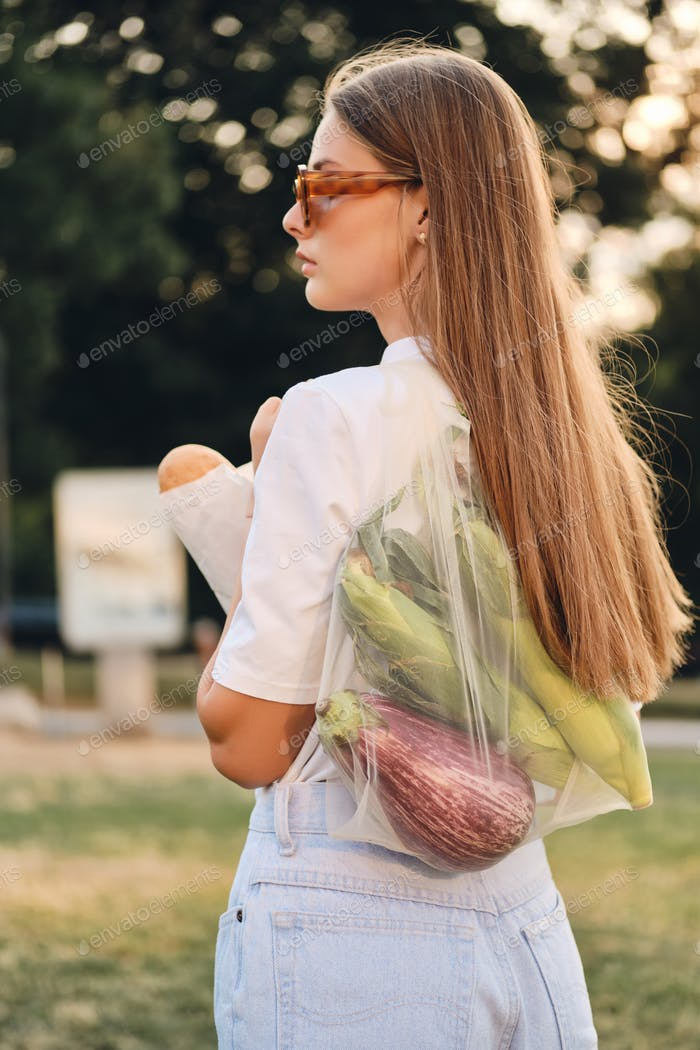 Young attractive woman standing with baguette bread and vegetables in eco bag on shoulder in park