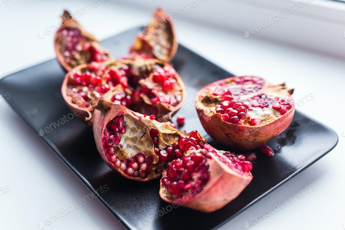 Big ripe red garnet. Fruits of red ripe pomegranate on the windows sill.