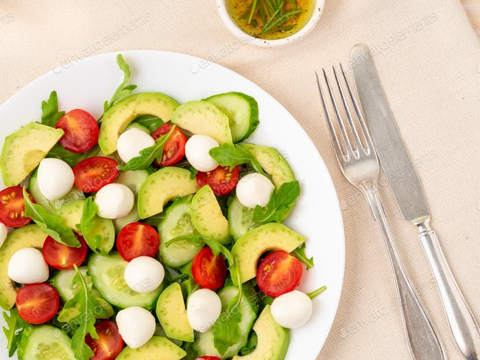 Fresh salad. Tomatoes, cucumbers, arugula, mozzarella, avocado. Fragrant oil