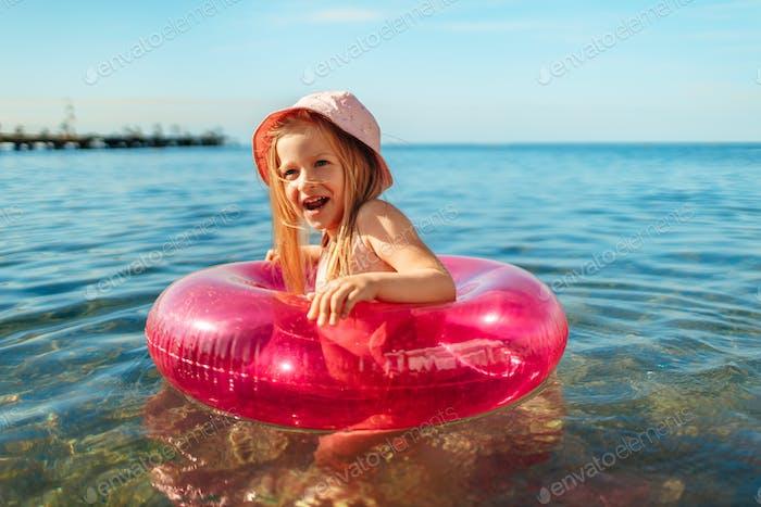 Mädchen Kind in rosa Panama schwimmt im Meer mit Kreis