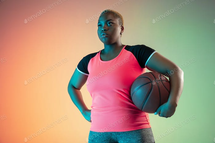 Young african-american plus size female model's training on gradient background