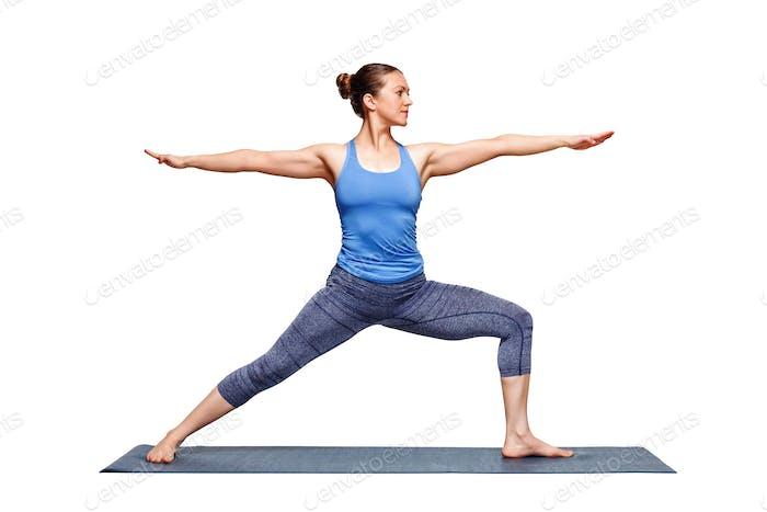 Sporty fit woman practices yoga asana utthita Virabhadras