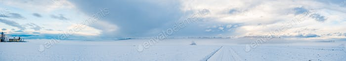 Panorama of agriculture fields covered with snow and fog in winter