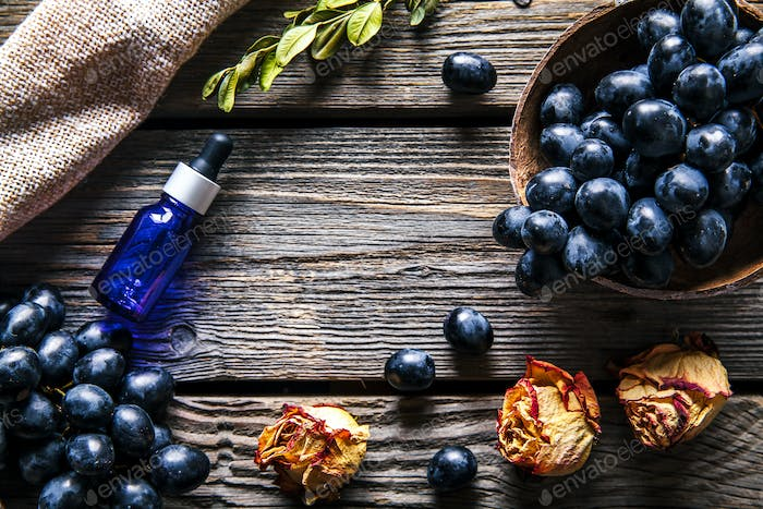 Grapes with dried roses and a jar of grape oil on a wooden background. Fruits, Flowers, Food