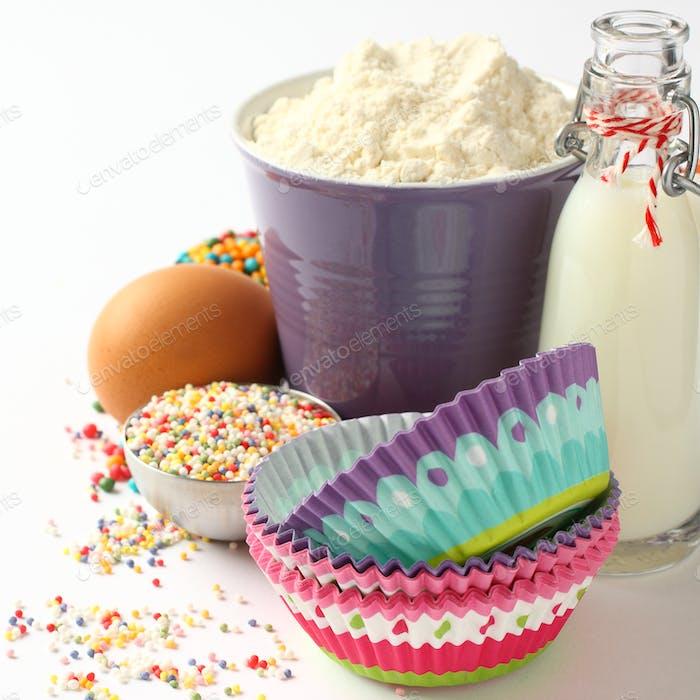 Cupcake-Förmchen und Zutaten über Weiß mit Copyspace