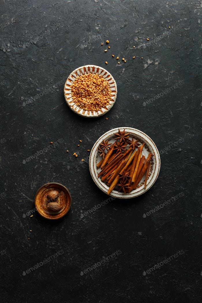 Cinnamon Sticks, star anise, nutmeg on a black background
