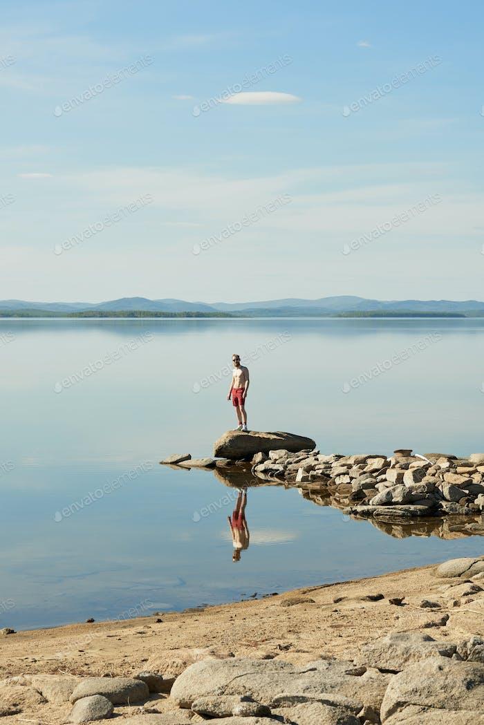 Hombre que pasa el día de verano en el lago