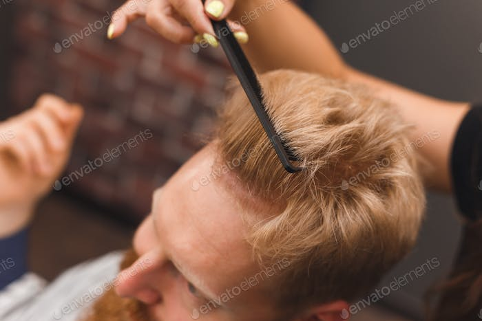 Hairdresser combs hair of handsome client before haircut in barbershop