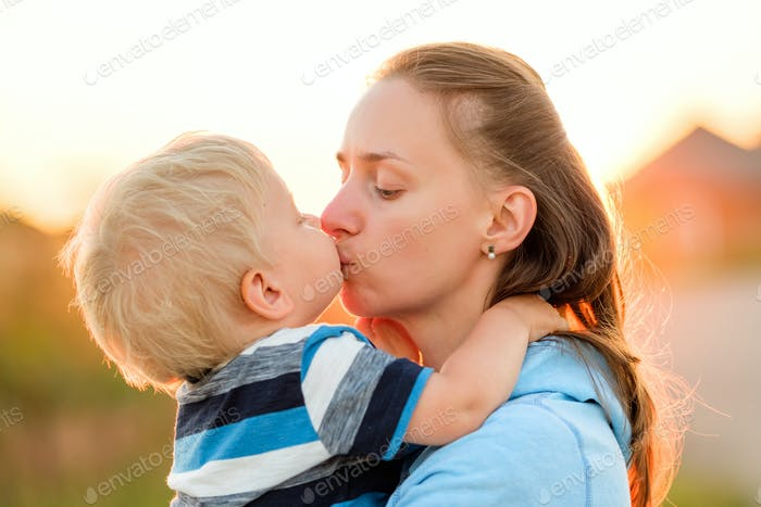 Woman and child outdoors at sunset. Boy kissing his mom.