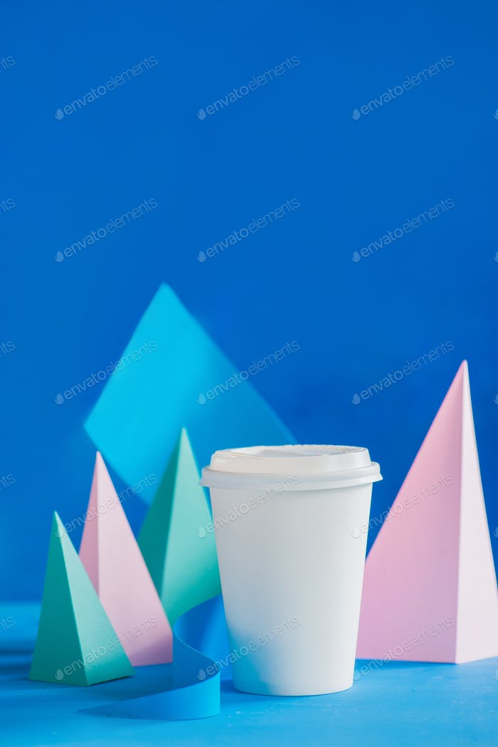 Blank mock-up paper cup in pastel colors with a modern paper craft sculpture on a vibrant background