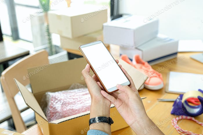 Online seller use mobile phone to take picture of products in box send to customer.
