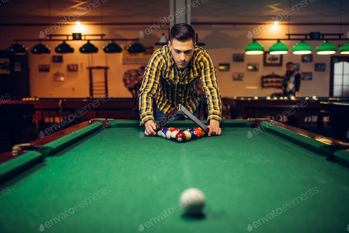 Male billiard player with pyramid places balls