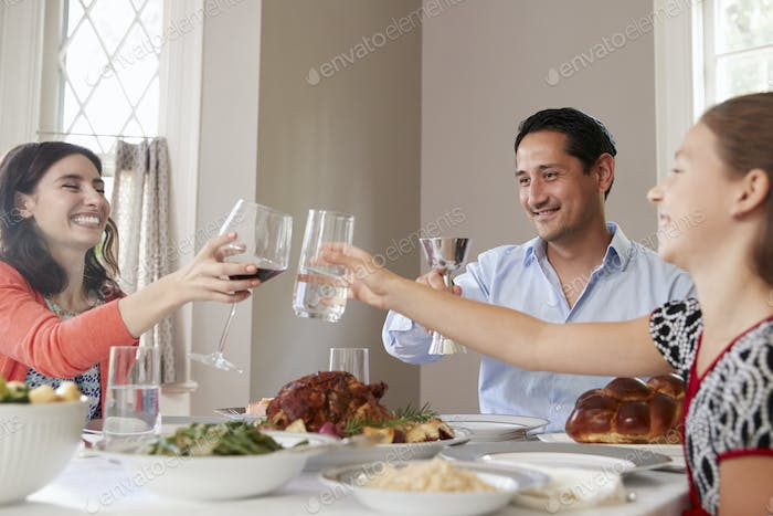 Jewish family raising glasses at the table for Shabbat meal
