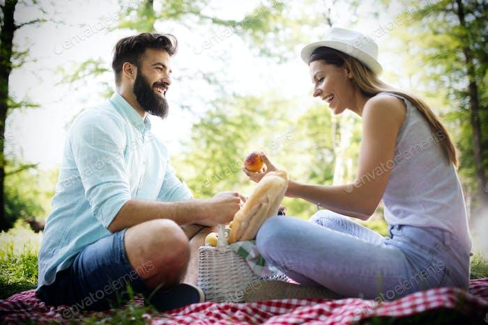 Glückliches junges Paar genießen ein Picknick im Park zusammen