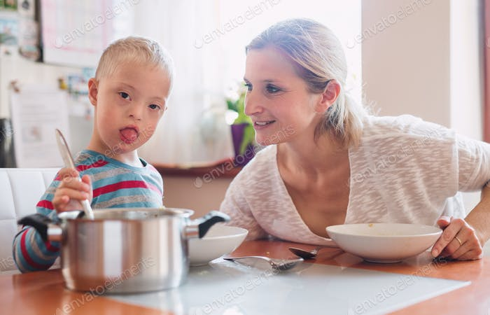 A handicapped down syndrome child with his mother indoors eating lunch.