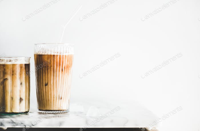 Iced latte coffee in glasses with straws on table, close-up