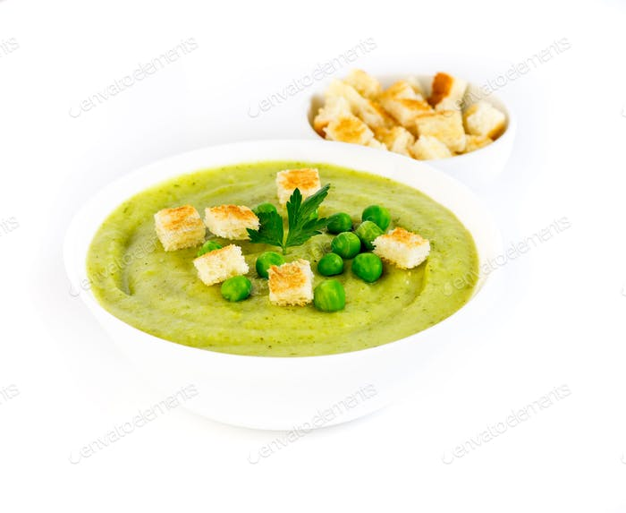 large white bowl with cream soup of broccoli, potatoes and green peas on white background, side view