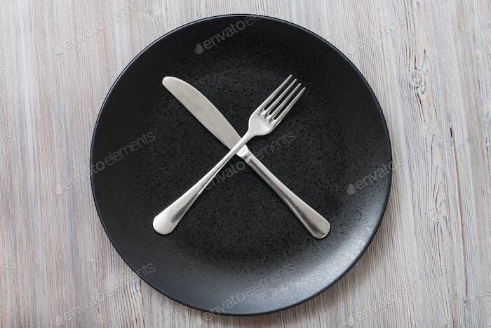 Draufsicht der schwarzen Platte mit Besteck auf grau