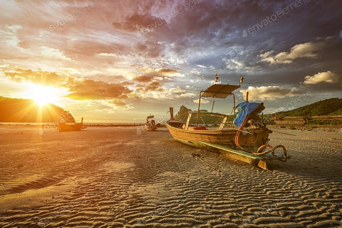Long tail boat at beach on sunset