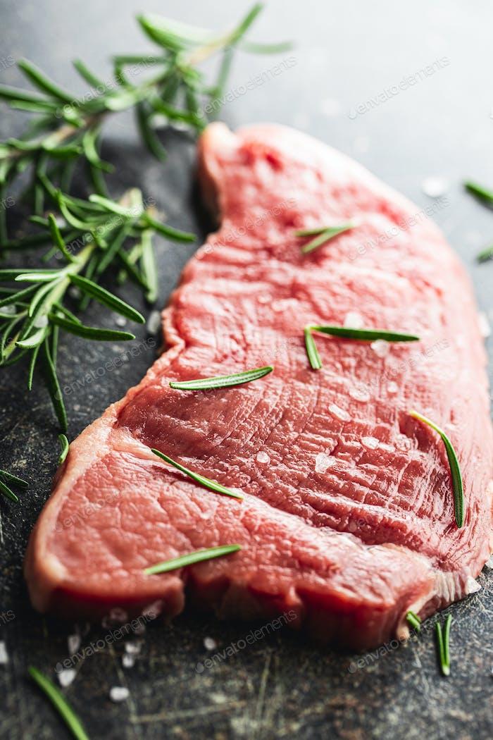 Rohes Kalbsschnitzel. Rohes Fleisch und Rosmarin