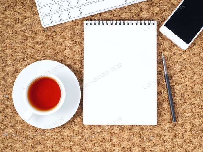Workplace with laptop and blank notepad on mat. Top view. Flat lay. Freelance desktop, warm climate