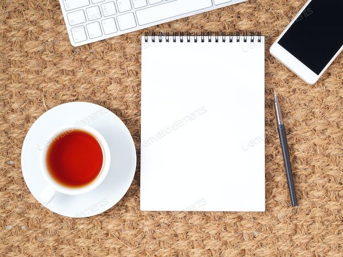 Arbeitsplatz mit Laptop und leerer Notizblock auf Matte. Draufsicht. Flache Lag. Freelance Desktop, warmes Klima