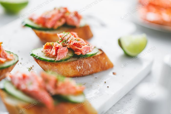 Toasts with fresh cucumber and smoked salmon served with lime shavings.
