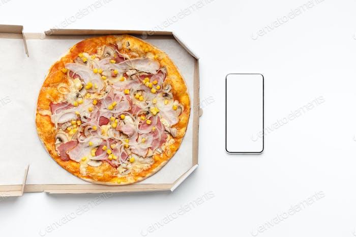 Lieferung von Lebensmitteln. Pizza in Box und Smartphone mit leerem Bildschirm