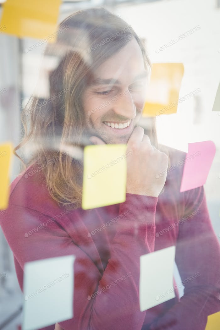 Happy creative businessman with hand on chin looking at sticky notes stuck on glass in office