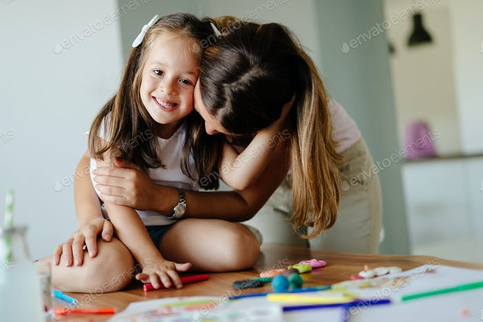Little girl doing art work with her mother