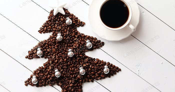 Beans in shape of fir and cup of coffee