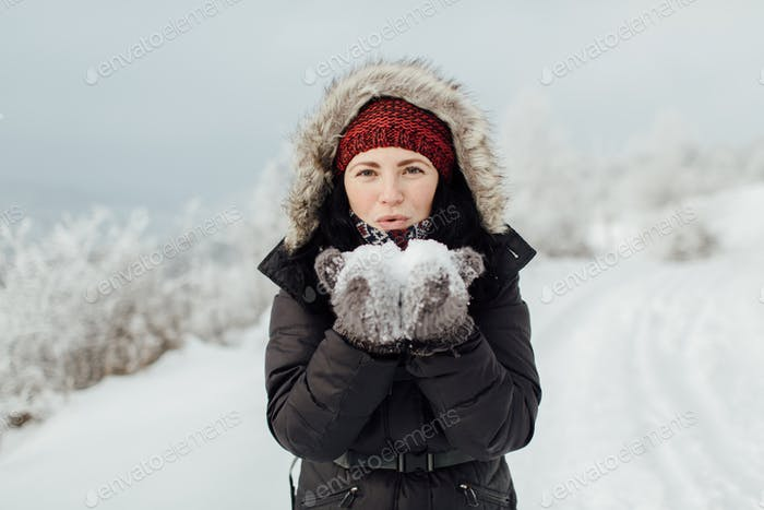Smiling woman dressed warm blowing off snow from her hands