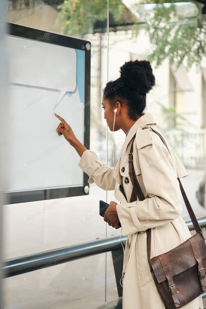 African American girl in stylish trench coat with cellphone thoughtfully watching route at bus stop