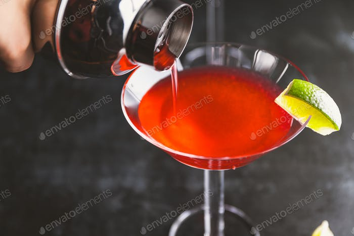Pouring red cocktail with lime in Martini glass on a table.