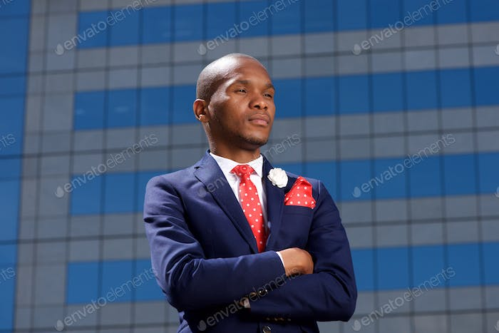 serious young african businessman standing in city