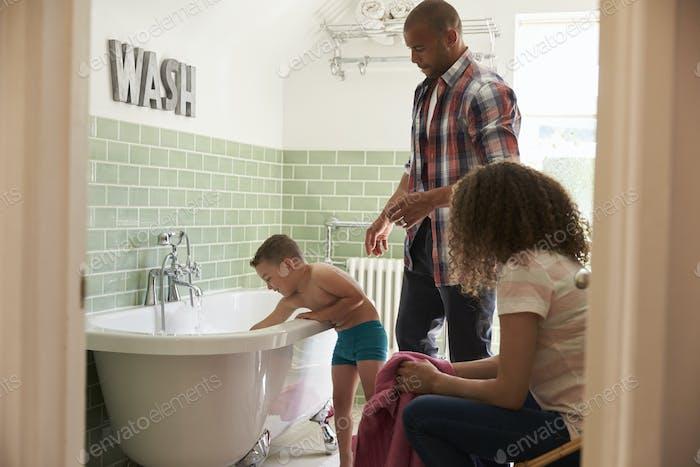 Parents And Son Having Fun At Bath Time Together