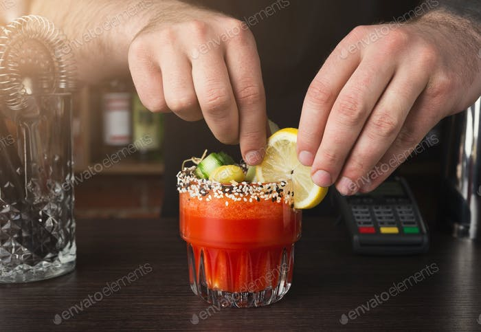 Hands of barman preparing cocktail at bar counter