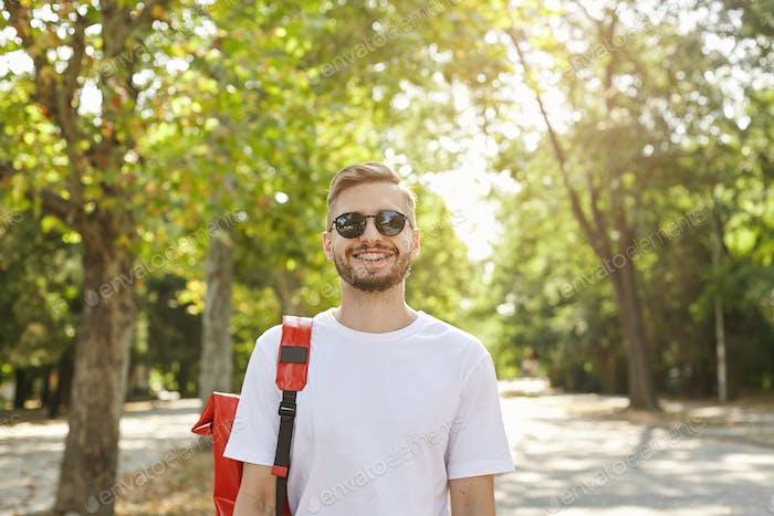 Porträt eines fröhlichen, gutaussehenden Mannes mit Stoppeln, mit Sonnenbrille und Freizeitkleidung